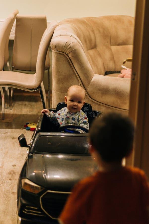 Dziecko siedzi w zabawkarskim samochodzie, bawi? si?, pr?buje i?? po drugie zerknięcia obraz royalty free
