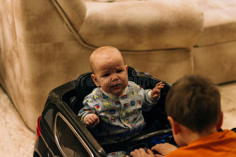 Dziecko siedzi w zabawkarskim samochodzie i drugi na kapiszonie, dziecko gry obraz stock