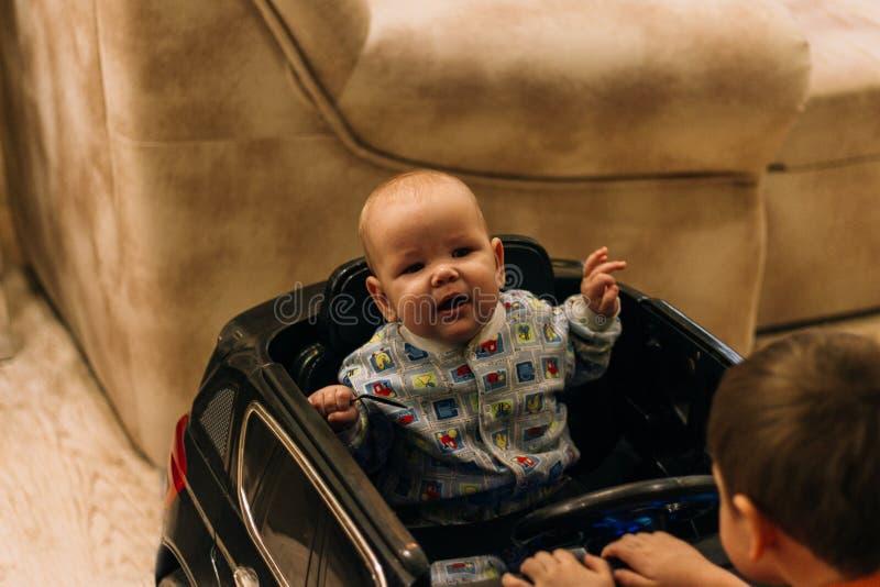 Dziecko siedzi w zabawkarskim samochodzie i drugi na kapiszonie, dziecko gry fotografia royalty free