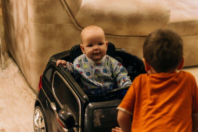 Dziecko siedzi w zabawkarskim samochodzie i drugi na kapiszonie, dziecko gry fotografia stock
