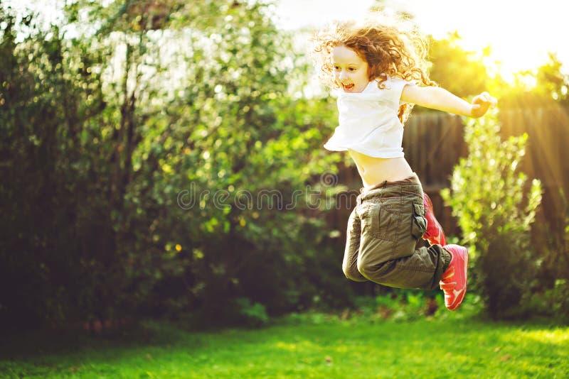 Dziecko skacze dalej outdoors szczęśliwy dzieciństwa pojęcie zdjęcia stock