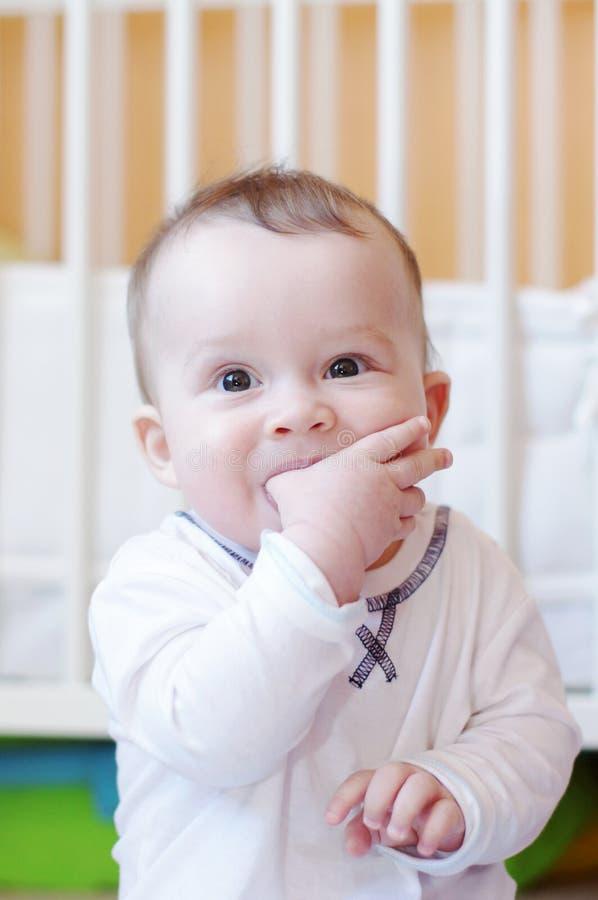 Dziecko ssa palec przeciw białemu łóżku fotografia stock