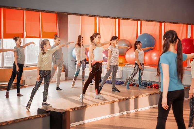 Dziecko stylu życia zdrowy pojęcie - grupa sportive nastoletnie dziewczyny ćwiczy w gym obraz royalty free