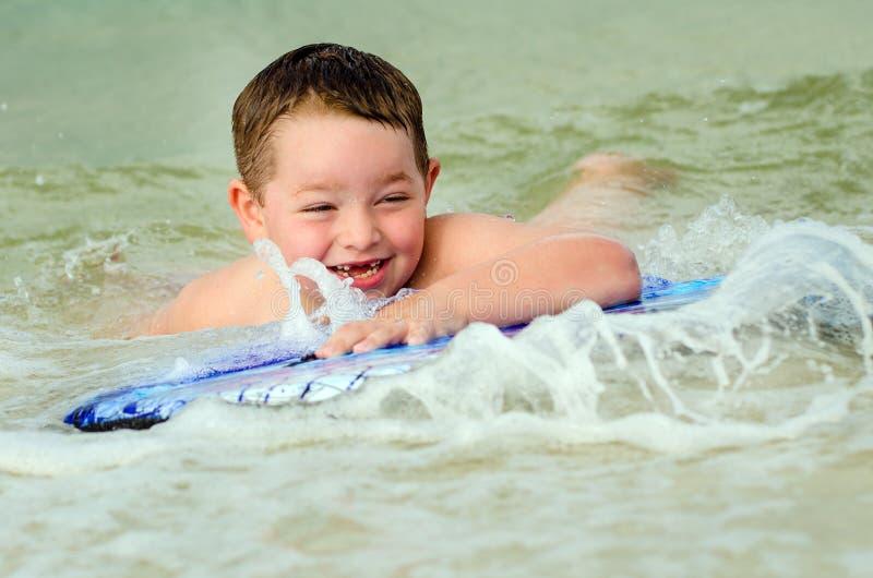 Dziecko surfing na bodyboard przy plażą obraz royalty free