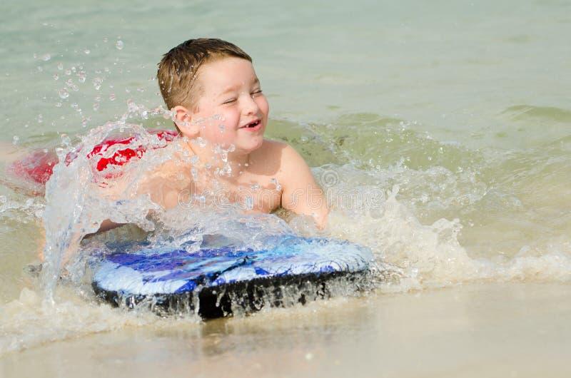 Dziecko surfing na bodyboard przy plażą fotografia stock