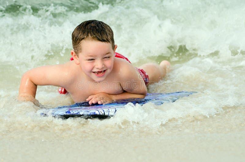 Dziecko surfing na bodyboard przy plażą zdjęcie royalty free