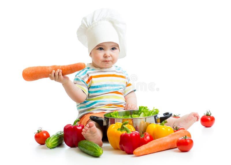 Dziecko szef kuchni z zdrowymi karmowymi warzywami zdjęcie royalty free