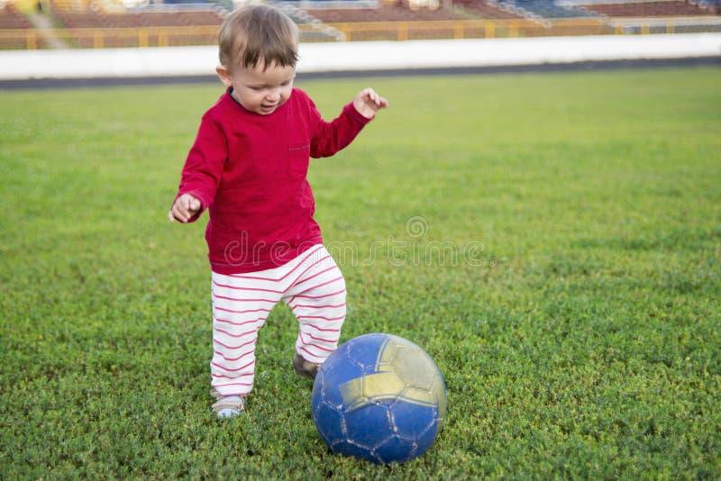 Dziecko sztuka z piłką w trawy polu, chłopiec bawić się futbol Aktywny dziecko w lecie z piłką zdjęcia stock
