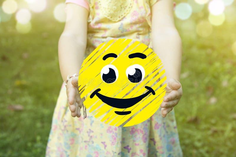 Dziecko trzyma szczęśliwą smiley ikonę jako sukcesu pojęcie outdoors na słonecznym dniu fotografia stock