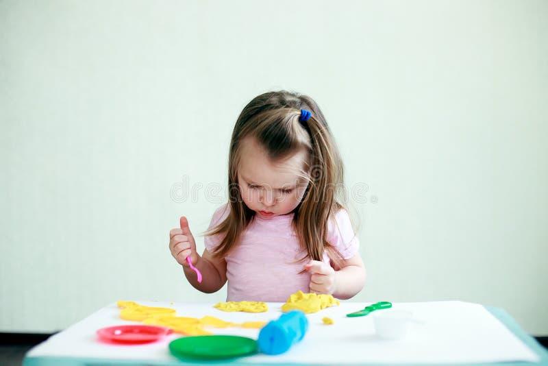 Dziecko twórczość Dzieciak sculpts od gliny Śliczny mały 2 roku dziewczyn lejni od plasteliny na stole w pokoju zdjęcie royalty free
