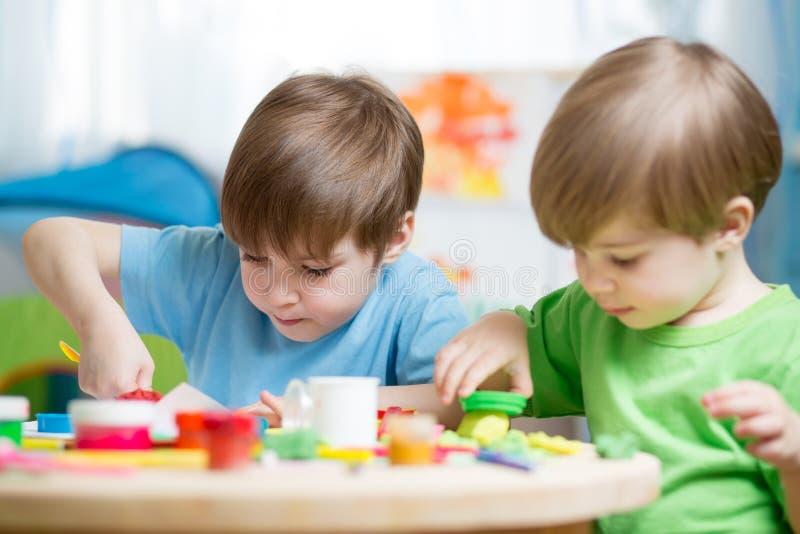 Dziecko twórczość Dzieciaki sculpting od gliny Śliczna chłopiec lejnia od plasteliny na stole w pepiniera pokoju fotografia royalty free