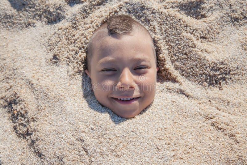 Dziecko twarz Zakopujący piasek obraz stock