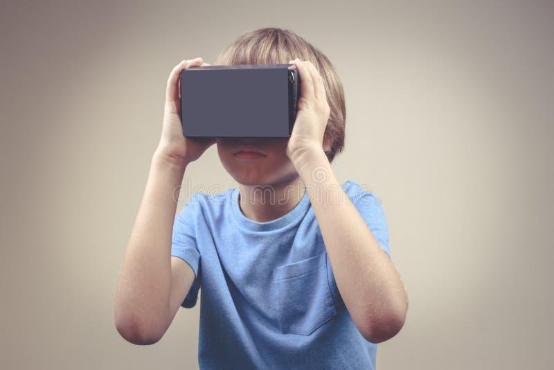 Dziecko używa nową rzeczywistość wirtualną, VR kartonu szkła obraz stock
