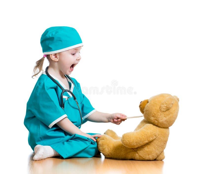 Dziecko ubierający jako lekarka bawić się z zabawką fotografia royalty free