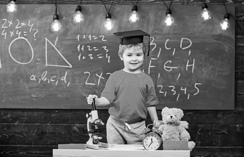 Dziecko, uczeń na uśmiechniętej twarzy blisko mikroskopu Pierwszy poprzedni zainteresowany w studiowaniu, edukacja Wunderkind poj zdjęcie stock