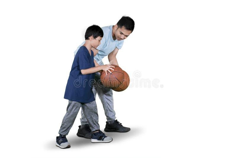Dziecko uczy się dryblować koszykówkę z jego ojcem fotografia stock