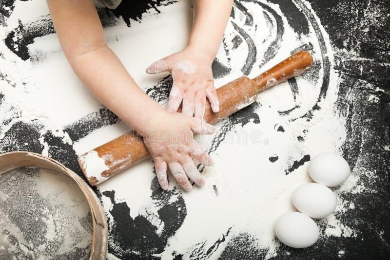 Dziecko uczy się gotować na czarnym stole z mąką w kuchni, obraz royalty free