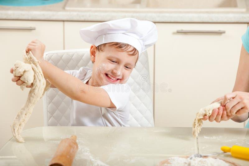 Dziecko ugniata ciasto w mące zdjęcia royalty free
