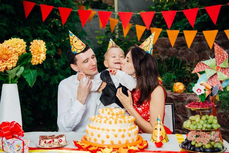 Dziecko urodziny temat rodzina trzy Kaukaskiego ludzie siedzi w podwórko dom przy świątecznym dekorującym stołem w śmiesznym h obraz royalty free