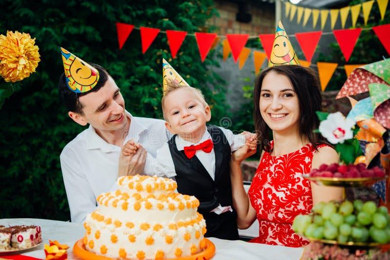 Dziecko urodziny temat rodzina trzy Kaukaskiego ludzie siedzi w podwórko dom przy świątecznym dekorującym stołem w śmiesznym h obrazy royalty free
