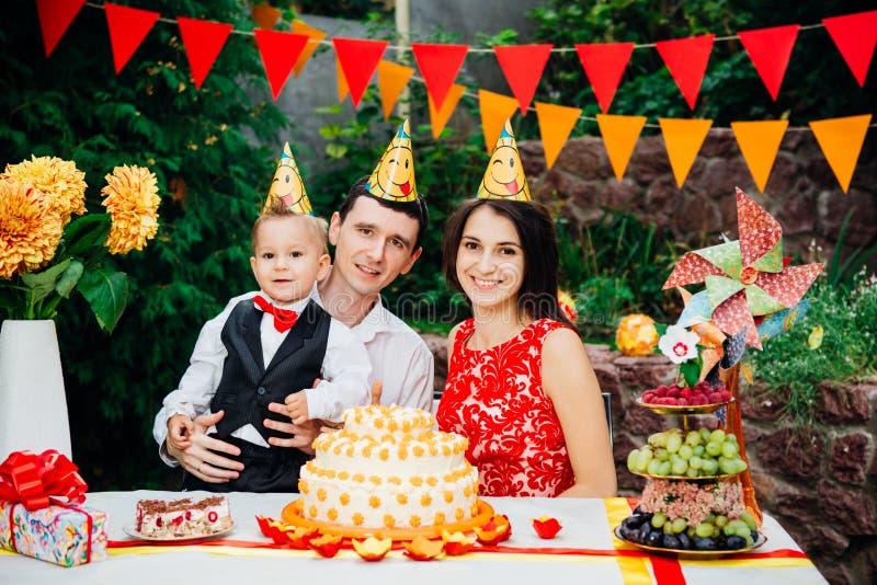 Dziecko urodziny temat rodzina trzy Kaukaskiego ludzie siedzi w podwórko dom przy świątecznym dekorującym stołem w śmiesznym h obrazy stock
