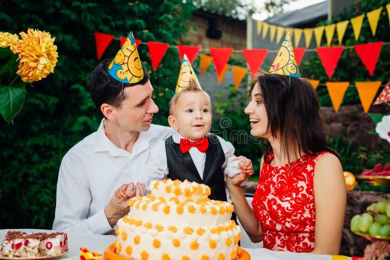 Dziecko urodziny temat rodzina trzy Kaukaskiego ludzie siedzi w podwórko dom przy świątecznym dekorującym stołem w śmiesznym h zdjęcie royalty free