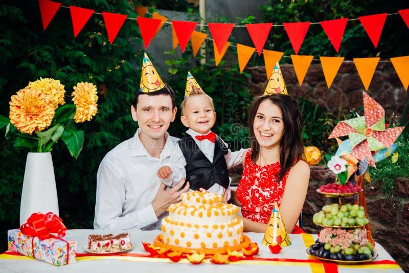 Dziecko urodziny temat rodzina trzy Kaukaskiego ludzie siedzi w podwórko dom przy świątecznym dekorującym stołem w śmiesznym h fotografia stock