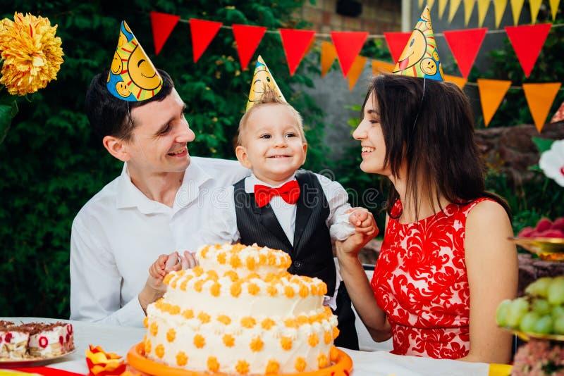 Dziecko urodziny temat rodzina trzy Kaukaskiego ludzie siedzi w podwórko dom przy świątecznym dekorującym stołem w śmiesznym h fotografia royalty free