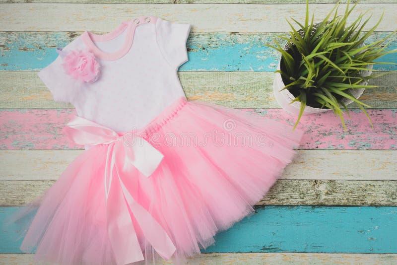 Dziecko ustawia różową tiul spódnicę, białego bodysuit serca i piękną różową kapitałkę nad pastelowym drewnianym tłem -, wierzcho zdjęcie royalty free