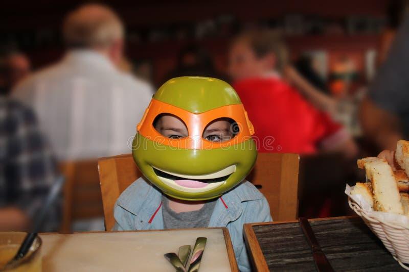 Dziecko w żółw masce przy stołem zdjęcie royalty free