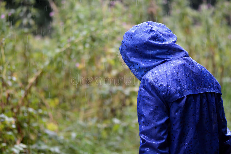 Dziecko w błękitnym wodoodpornym żakiecie w deszczu zdjęcia royalty free