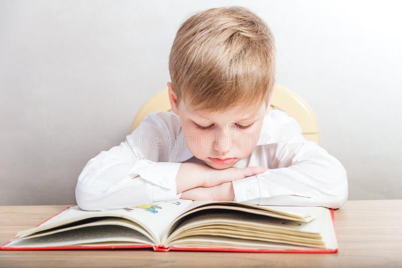 Dziecko w białym koszulowym obsiadaniu z książką przy jego biurkiem obrazy royalty free