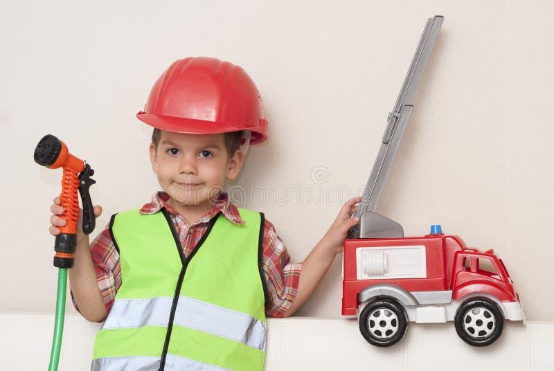 Dziecko w czerwonym hełmie z pożarniczym silnikiem i obrazy stock