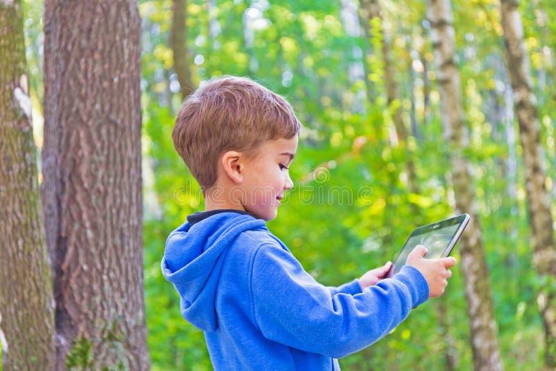 Dziecko w drewnach z pastylka komputerem osobistym zdjęcia stock
