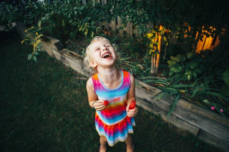 Dziecko w kolorowym smokingowym bieg w ogródzie na domowym podwórku fotografia royalty free