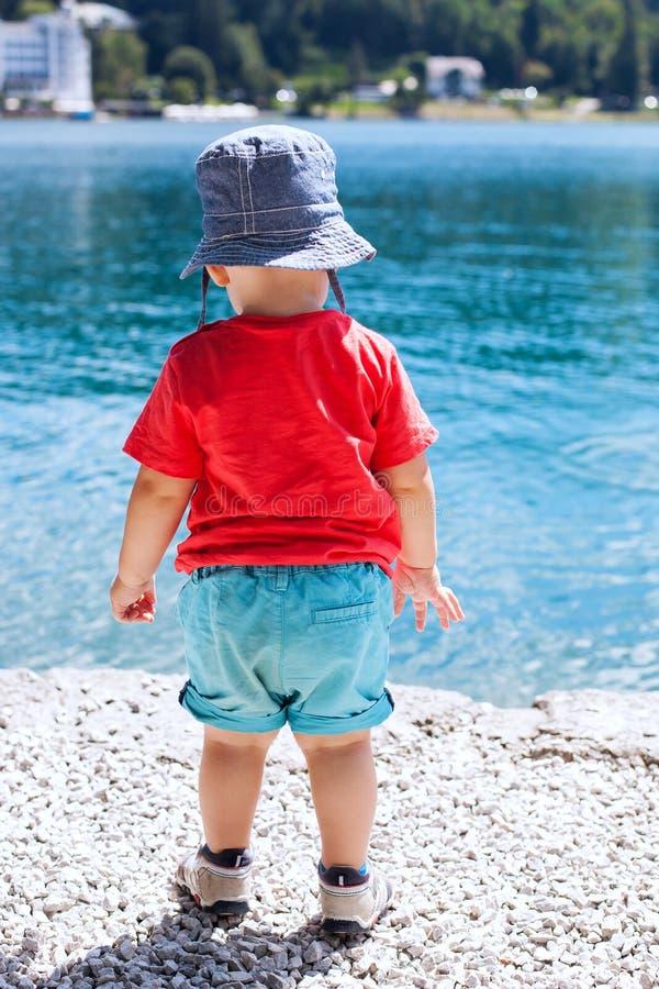 Dziecko w lecie odziewa na tle jaskrawa błękitne wody zdjęcie royalty free