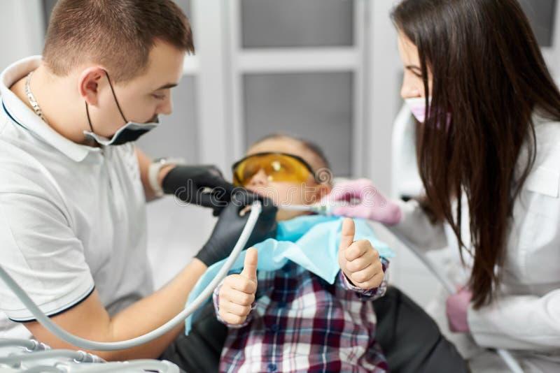 Dziecko w pomarańczowych stomatologicznych szkłach howing aprobaty podczas gdy mieć stomatologicznego traktowanie zdjęcie royalty free
