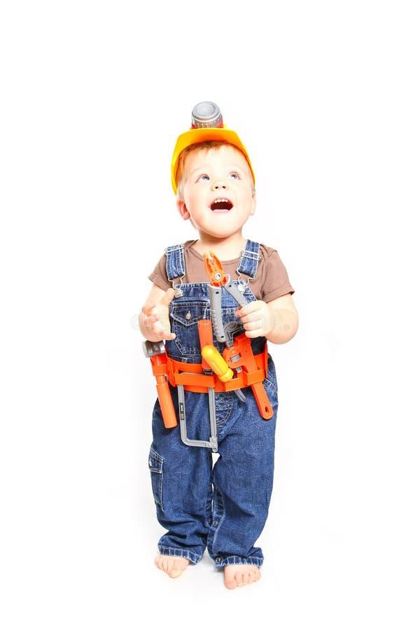 Dziecko w pomarańczowym hełmie z narzędziami na białym tle zdjęcia royalty free