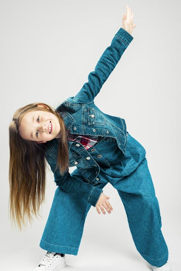 Dziecko w ruchu dzieciak mody mała dziewczynka robi ruchowi z ona rękom i nogom dziecko taniec t?a mu?ni?cia zako?czenie odizolow zdjęcia stock