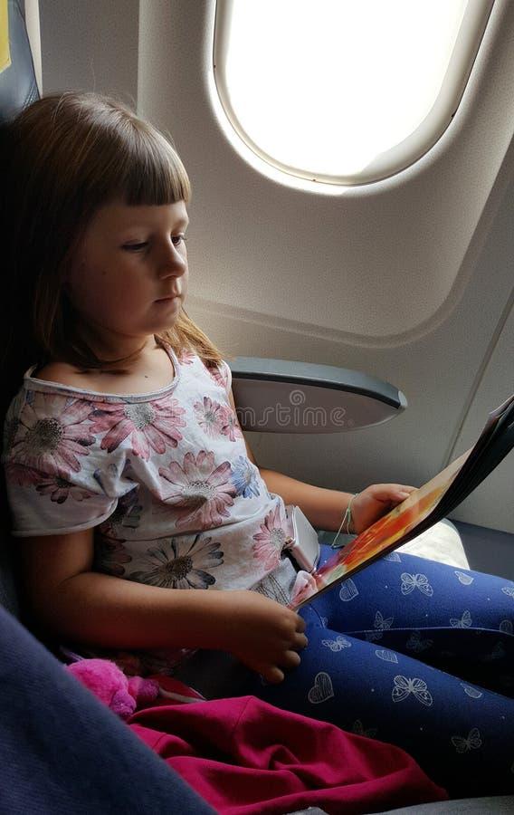 Dziecko w samolocie czyta książkę obraz royalty free