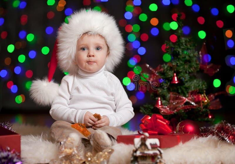 Dziecko w Santa kapeluszu na jaskrawy świątecznym tle obrazy royalty free