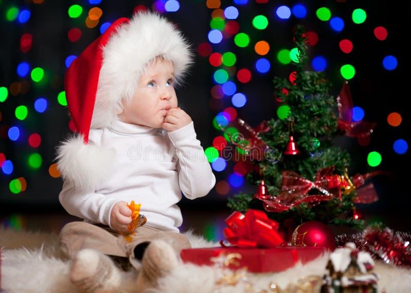 Dziecko w Santa kapeluszu na jaskrawy świątecznym tle obrazy stock