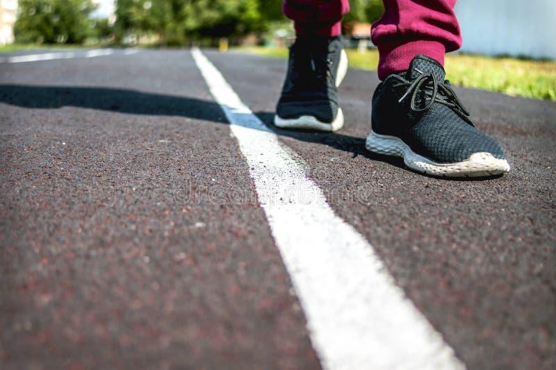 Dziecko w Sneakers Chodzi wzdłuż Białej linii przy bieg śladem na letnim dniu Robić wyborowi, Krzyżuje granicę ograniczenie obraz royalty free