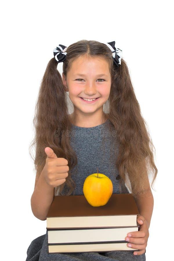 Dziecko w wieku szkolnym z stertą książki i jabłko pokazuje aprobaty zdjęcie royalty free