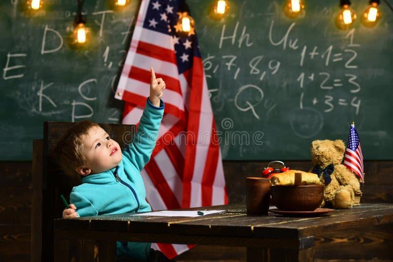 Dziecko w wieku szkolnym z usa flaga, tła zielony blackboard w szkole, dzień niepodległości zdjęcie stock