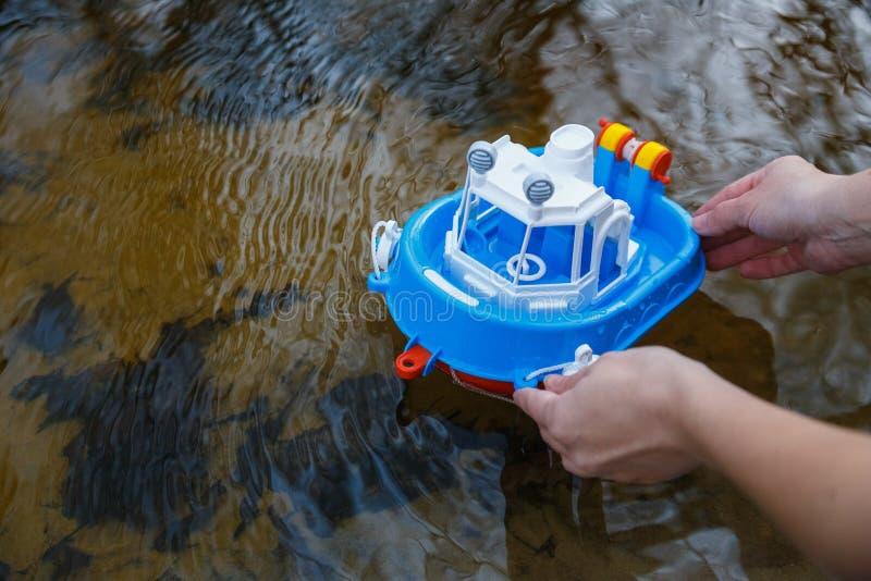 Dziecko wszczyna łódź w lasowej rzece obrazy stock
