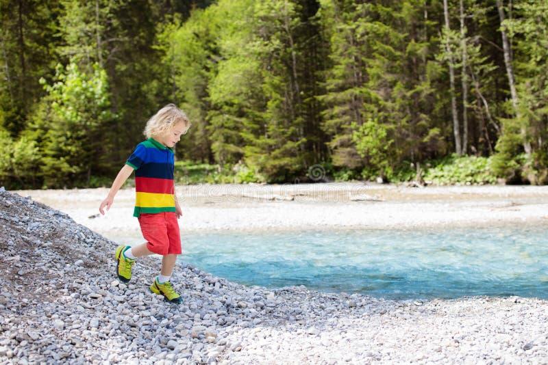 Dziecko wycieczkuje w górach Dzieciaki przy rzecznym brzeg obrazy royalty free