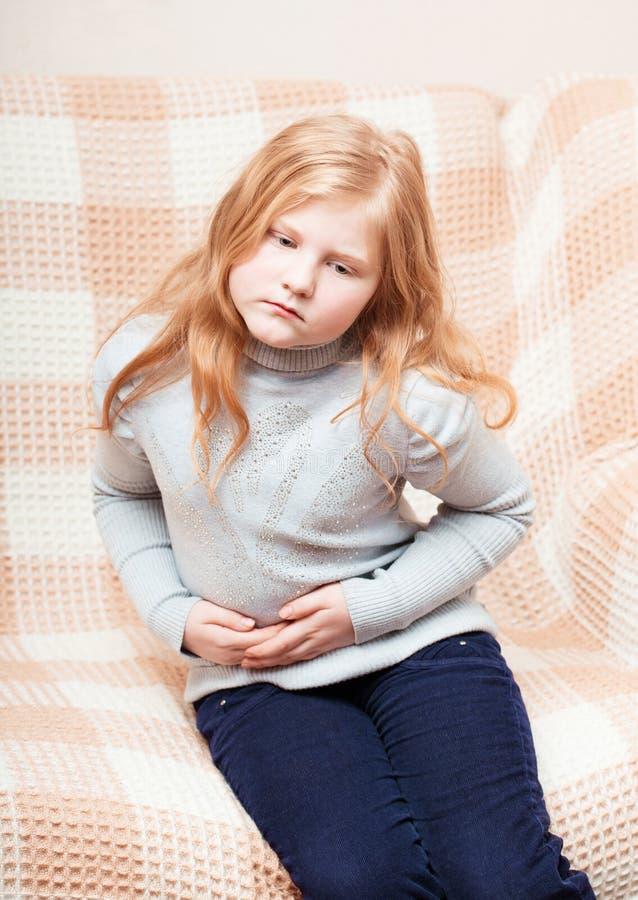 Dziecko z żołądek obolałością w kanapie obrazy royalty free