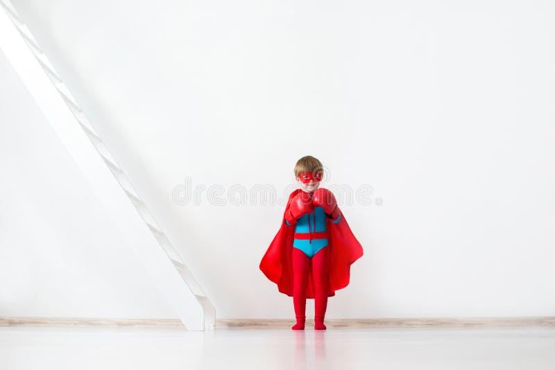 Dziecko z bokserskimi rękawiczkami i czerwoną peleryną obrazy stock