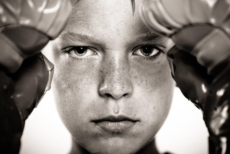 Dziecko z bokserskimi rękawiczkami skupia się na uderzać pięścią ochraniacza zdjęcia stock